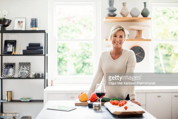 Smiling mature woman standing at kitchen island