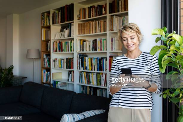 smiling mature woman standing at the window in living room at home using smartphone - mature woman fotografías e imágenes de stock