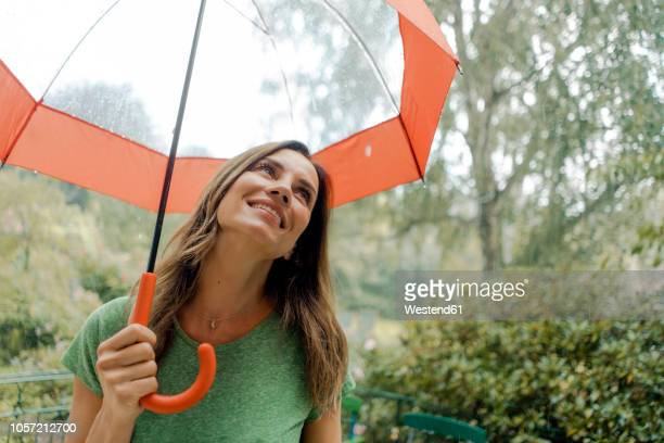 smiling mature woman standing in rain under umbrella - women in wet t shirts stock pictures, royalty-free photos & images