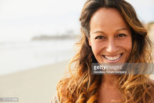 glimlachende rijpe vrouw die zich op een zandig strand bevindt - alleen één oudere vrouw stockfoto's en -beelden