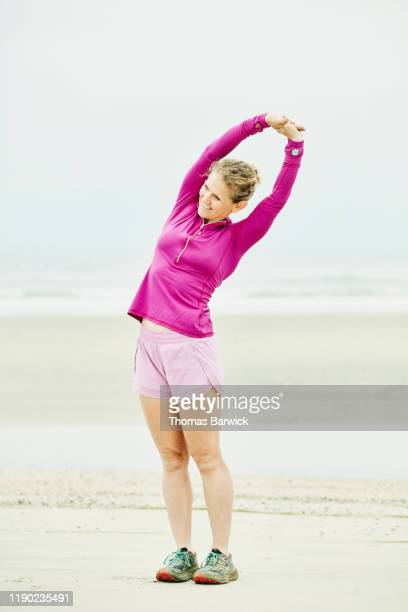 smiling mature woman stretching on beach before early morning run - ショッキングピンク ストックフォトと画像