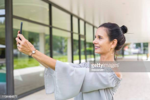 smiling mature woman taking selfie with smartphone outdoors - opgestoken haar stockfoto's en -beelden