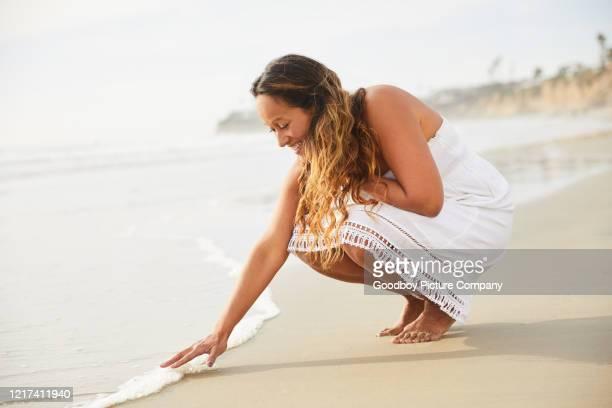 lächelnde reife frau berührt die eingehende brandung am strand - weißes kleid stock-fotos und bilder
