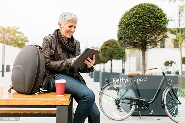 Smiling Mature Woman Using Digital Tablet Outdoors.