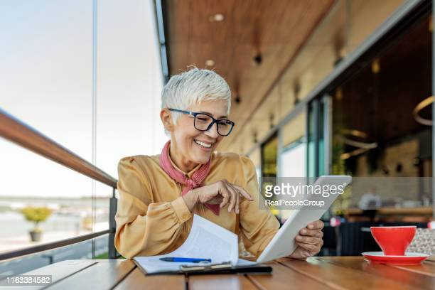 smiling mature woman using digital tablet - short hair stock pictures, royalty-free photos & images