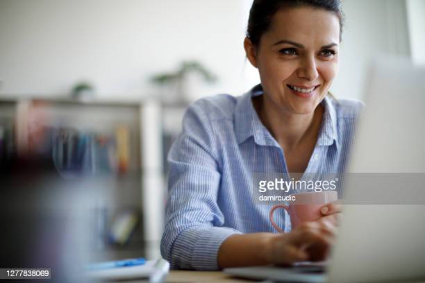 lächelnde reife frau mit laptop für die arbeit zu hause - weibliche angestellte stock-fotos und bilder