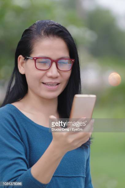 Smiling Mature Woman Using Mobile Phone