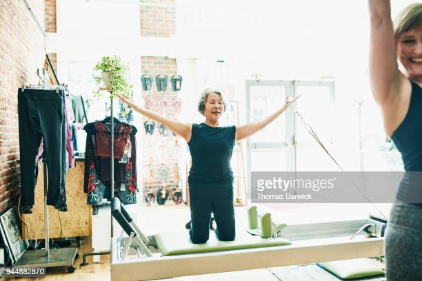 Smiling mature woman using pilates reformer to strengthen shoulders during class in fitness studio