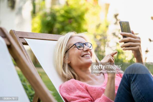 smiling mature woman using smartphone while sitting on deckchair - one mature woman only stock pictures, royalty-free photos & images