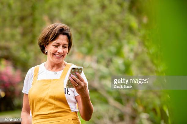 sonriente mujer madura video llamando a un teléfono afuera en su patio - mujeres de mediana edad fotografías e imágenes de stock