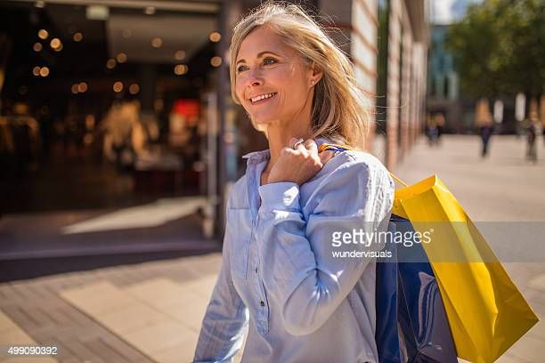 Smiling mature woman walking with shopping bags in town