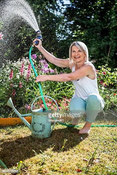 Smiling mature woman watering flowers in garden