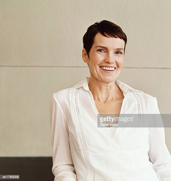 smiling mature woman wearing a white shirt - capelli neri foto e immagini stock