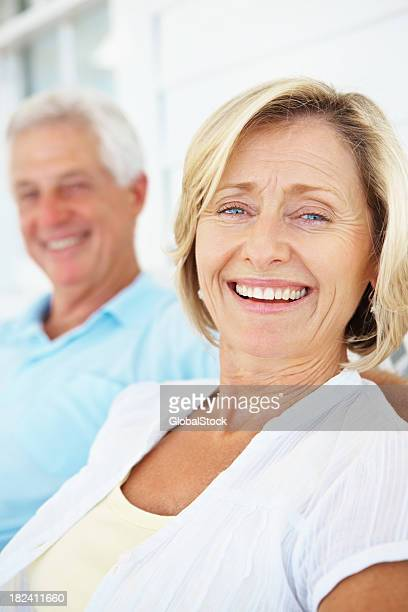 Smiling mature woman with a man in background