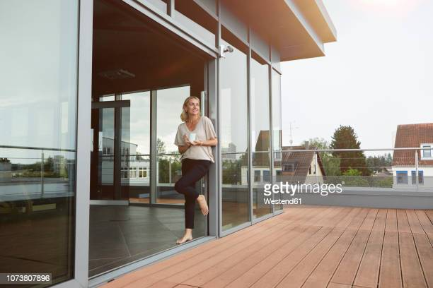 smiling mature woman with cup of coffee standing at roof terrace at home - reichtum stock-fotos und bilder