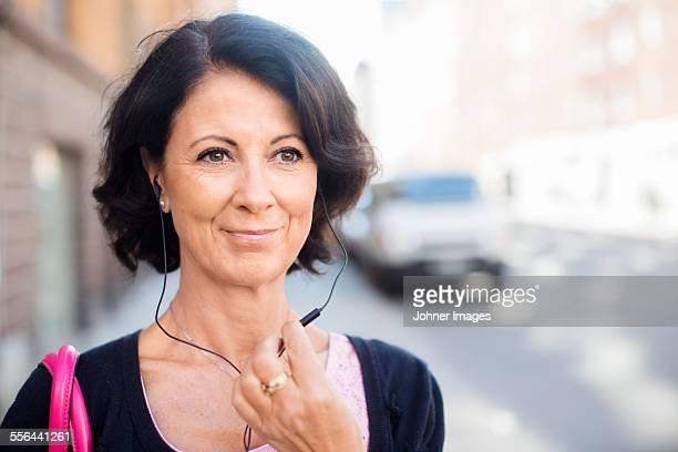 smiling mature woman with earphones - 55 59 años fotografías e imágenes de stock