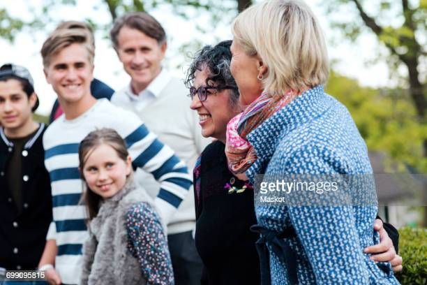 smiling mature woman with family and friends at yard - family reunion stock pictures, royalty-free photos & images