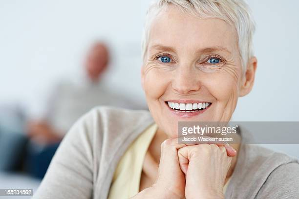 Smiling mature woman with husband in the background