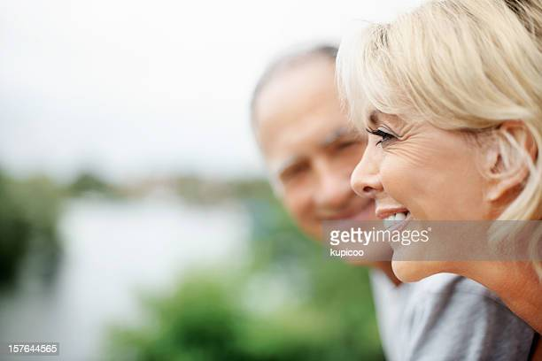 Smiling mature woman with husband looking at her