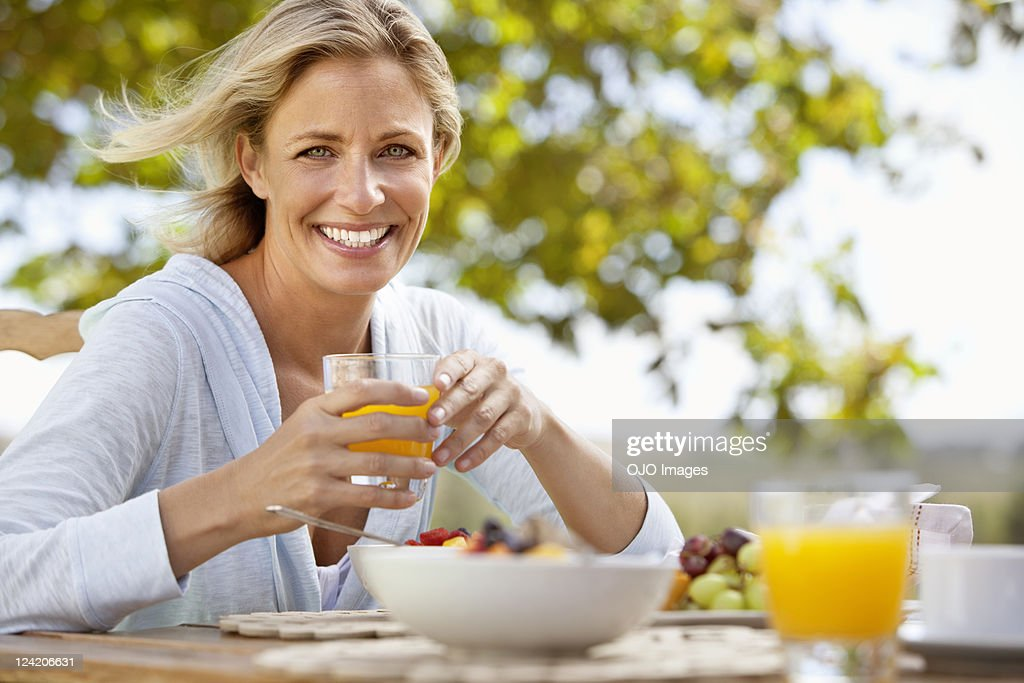 Smiling mature woman with orange juice at breakfast table outdoors : Stock Photo