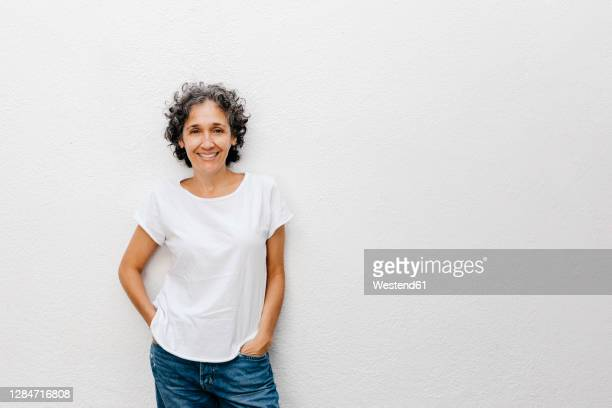 smiling mature woman with short hair standing against white wall - curly stock pictures, royalty-free photos & images