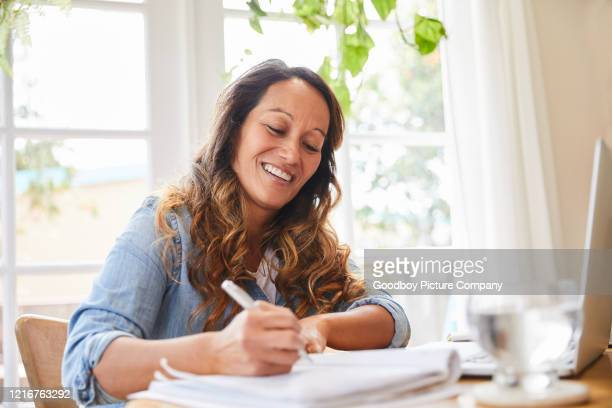 smiling mature woman writing in a notebook while working from home - writer stock pictures, royalty-free photos & images