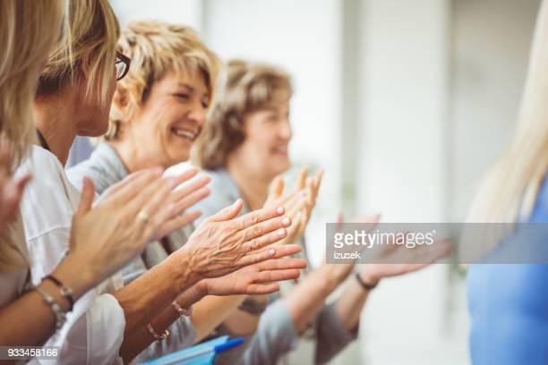 Femmes mûres souriantes, claquements de mains au cours du séminaire