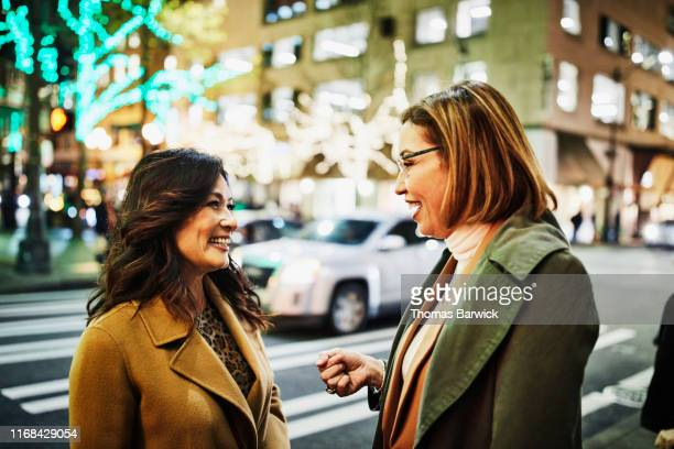 smiling mature women in discussion on street corner while holiday shopping on winter evening - camel active stock-fotos und bilder