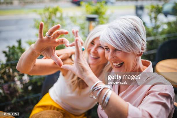 smiling mature women making heart shape with fingers - heart shape stock pictures, royalty-free photos & images