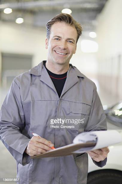 Smiling mechanic writing on clipboard
