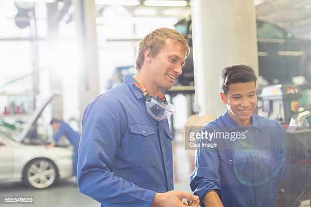 Smiling mechanics using computer in auto repair shop