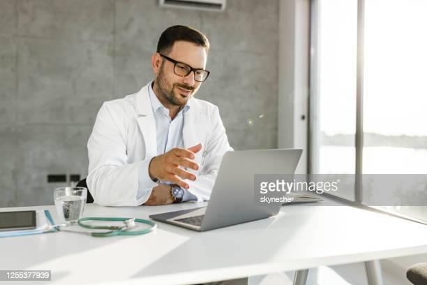 smiling medical expert having a video call over laptop in the office. - doutor imagens e fotografias de stock