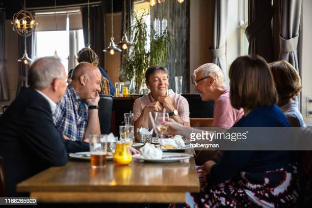smiling men and women enjoying pub lunch - medium group of people stock pictures, royalty-free photos & images