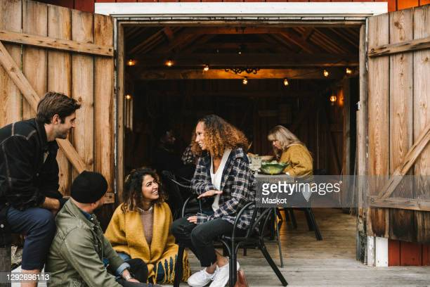 smiling men and women talking while sitting by cottage doorway during social gathering - sweden stock pictures, royalty-free photos & images