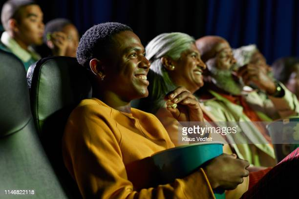 smiling men and women watching comedy film in theater - comedy film stock pictures, royalty-free photos & images