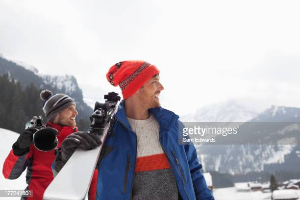 Sonriente hombre transporte esquís en la base de las montañas