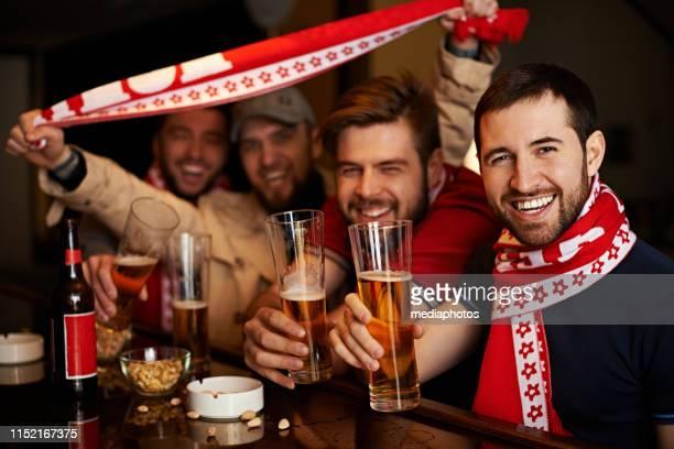 lächelnde männer feiern gewinn des sportteams - club football stock-fotos und bilder