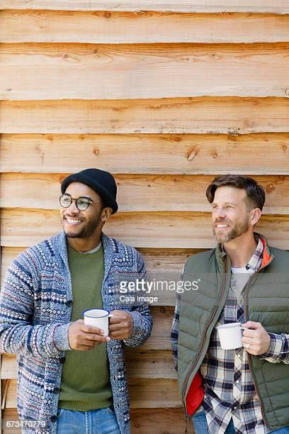 Smiling men drinking coffee outside cabin