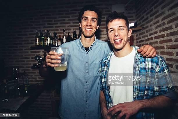 Smiling men drinking in nightclub