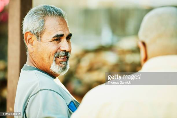 smiling men in discussion during backyard family barbecue - goatee stock pictures, royalty-free photos & images