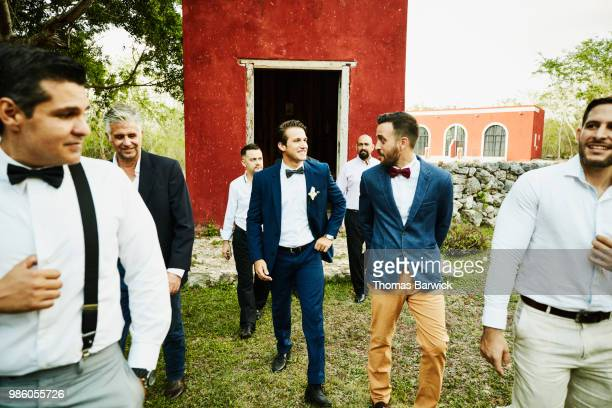 smiling men in wedding party walking to reception after having photo taken in front of chapel - wedding after party stock pictures, royalty-free photos & images