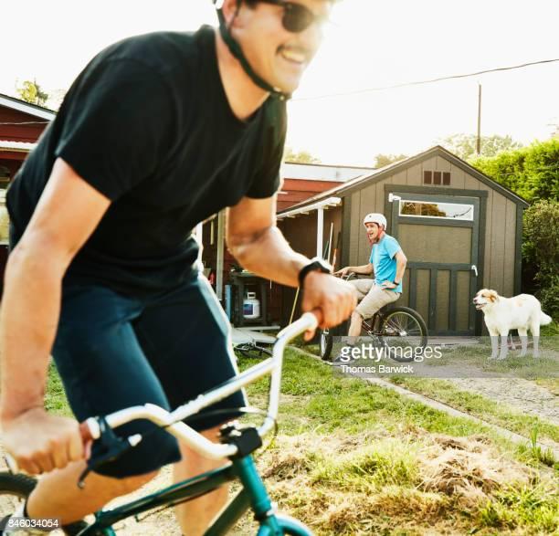 Smiling men riding BMX bikes on backyard dirt track on summer evening