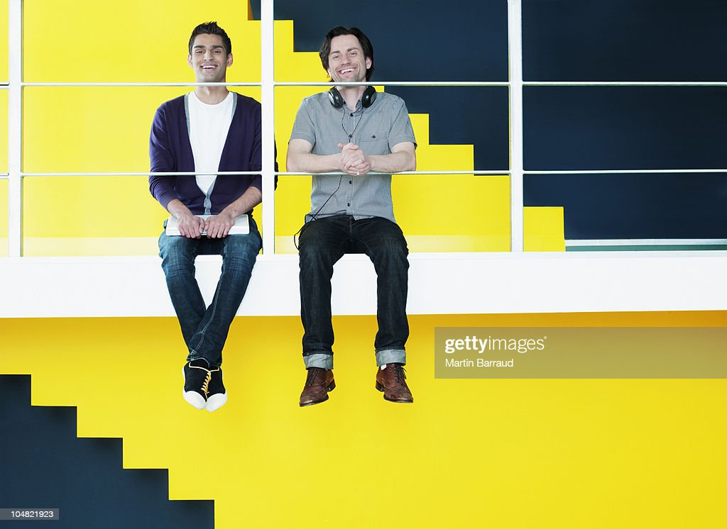 Smiling men sitting on ledge : Stock Photo