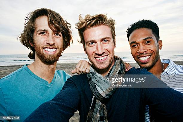 smiling men taking selfie on beach - three people stock pictures, royalty-free photos & images