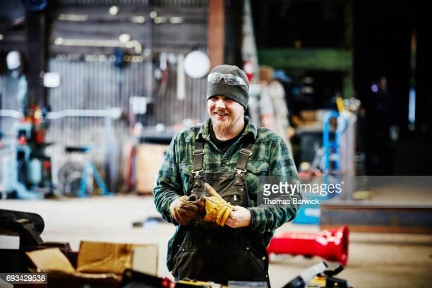 Smiling metal worker in metal workshop