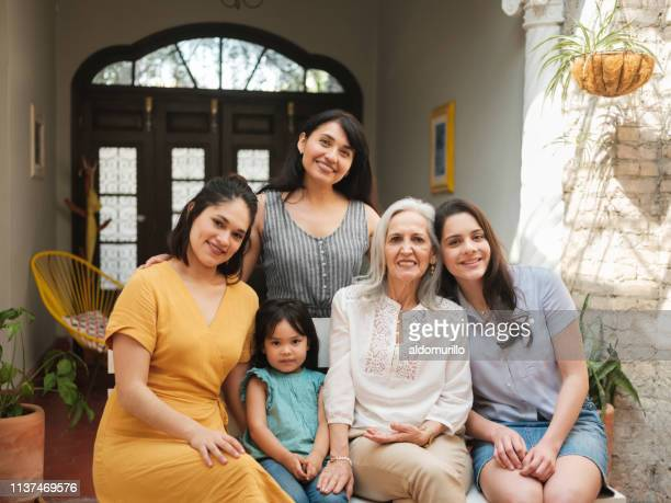 smiling mexican women sitting closely together - mexican mothers day stock photos and pictures