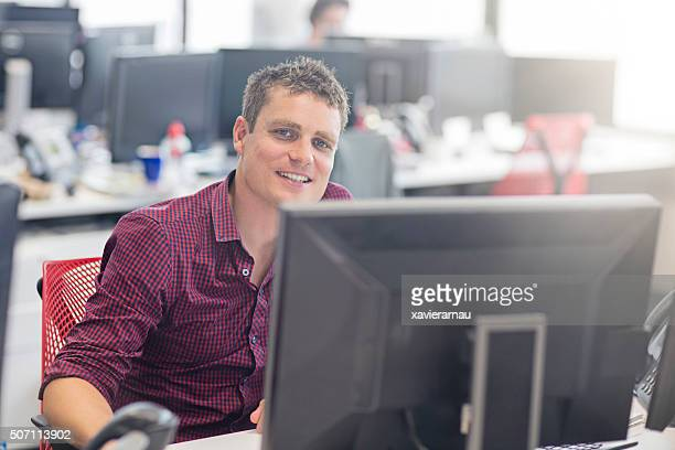 Smiling mid adult businessman sitting at his desk