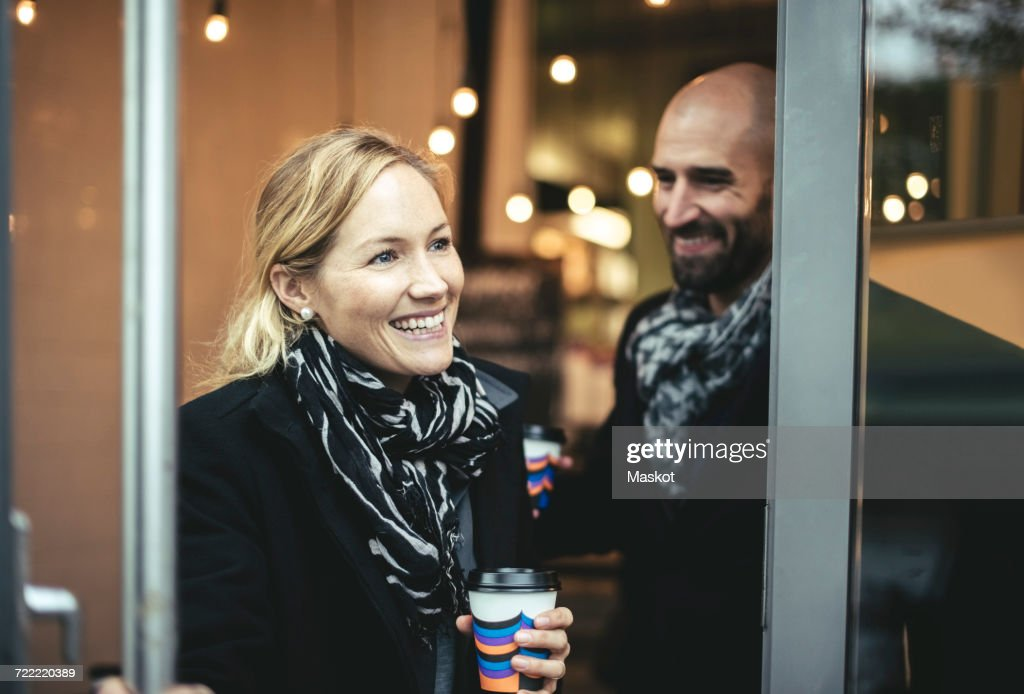 Smiling mid adult businesswoman and businessman leaving cafe : Stock Photo
