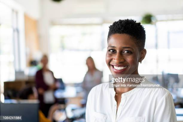 smiling mid adult businesswoman at office - 30 34 years stock pictures, royalty-free photos & images