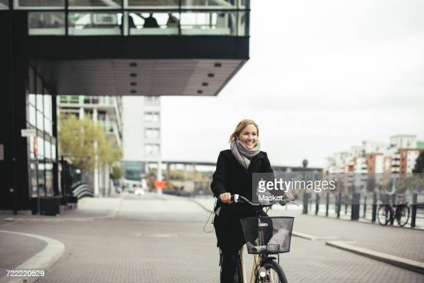 Smiling mid adult businesswoman riding bicycle on city street